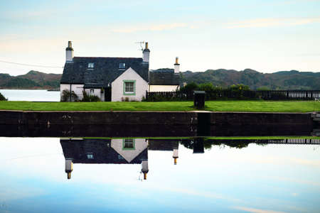 Crinan canal at sunrise. Colorful morning clouds and warm sunlight. Country houses and yachts close-up. Argyll and Bute, Scotland, UK Zdjęcie Seryjne