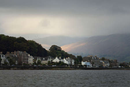 Storm sky. Panoramic view of a small town Rothesay from the water. Country houses and cars close-up. Forests, hills and mountains in the background. Bute Island, Firth of Clyde, Scotland, UK