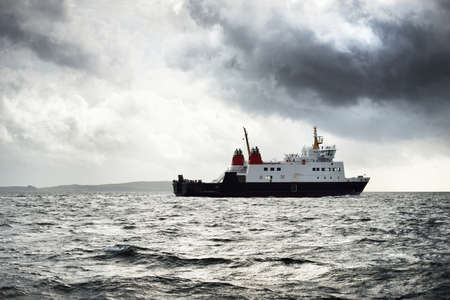 Storm sky. A cargo ship with cranes in the Firth of Clyde. Forests, hills and mountains of the Bute Island in the background. Scotland, UK