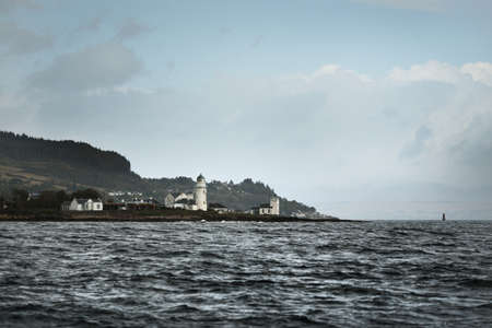 Panoramic view of the rocky river shores from the water. Trees, hills and mountains in the background. Lighthouse and country houses close-up. Cloudy blue sky. Gare Loch, Firth of Clyde, Scotland, UK Zdjęcie Seryjne