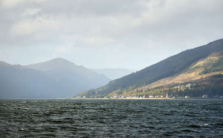 Panoramic view of the rocky river shores from the water. Country houses, trees, hills and mountains in the background. Cloudy blue sky. Gare Loch, Firth of Clyde, Scotland, UK Zdjęcie Seryjne