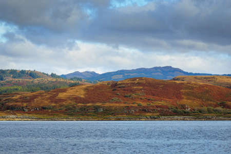 Panoramic view of the rocky river shores from the water. Trees, hills and mountains in the background. Cloudy blue sky. Gare Loch, Firth of Clyde, Scotland, UK Zdjęcie Seryjne