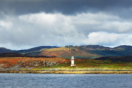 Panoramic view of the rocky river shores from the water. Trees, hills and mountains in the background. Lighthouse close-up. Cloudy blue sky. Gare Loch, Firth of Clyde, Scotland, UK