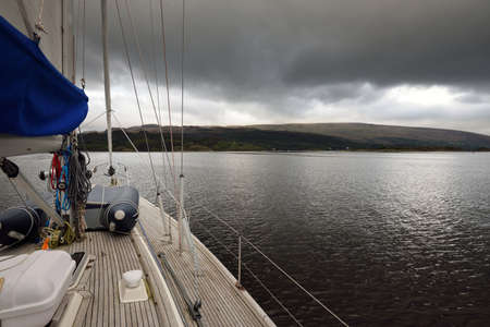 Dark storm sky. Sloop rigged modern yacht with wooden teak deck sailing on a cloudy day. A view from the deck to the bow. Panoramic view of the rocky shores of Kyles of Bute from the water. Hills and mountains in the background. Bute island, Firth of Clyde, Scotland, UK Zdjęcie Seryjne
