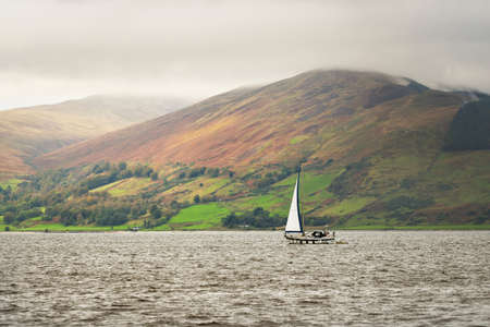 Dark storm sky. Sloop rigged yacht with a motor boat sailing on a cloudy day. Panoramic view of the rocky shores of Kyles of Bute from the water. Hills and mountains in the background. Bute island, Firth of Clyde, Scotland, UK