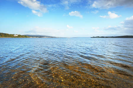 Panoramic view from the shore of Gare Loch near small village Rhu, Scotland, UK. Blue sky, crystal clear water. Travel destinations, vacations, recreation, tourism Zdjęcie Seryjne