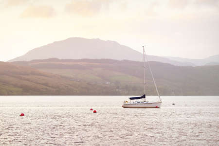 Stunning sunset cloudscape. Sloop rigged yachts and wooden boats anchored on mooring near the shore of a small village Rhu, Scotland, UK