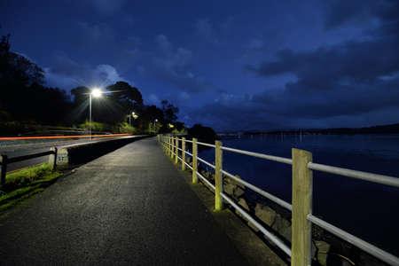 An empty illuminated promenade (asphalt road) near the lake shore of a small village Rhu at night. Scotland, UK. Twilight sky. Vacations, recreation, transportation, travel destinations