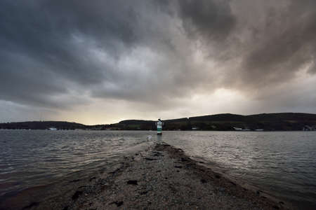Rocky lake shores and lighthouse under the colorful evening sky after the rain. Dramatic cloudscape. Gare Loch, Rhu, Scotland, UK Zdjęcie Seryjne