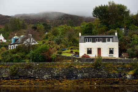 Cloudy autumn day. A view of the shores of Tarbert from the water. Country houses close-up. Scotland, UK