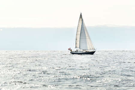 Blue sloop rigged yacht sailing in an open Baltic sea on a clear day, close-up. Riga bay, Latvia. Cruise, sport, recreation, leisure activity concepts