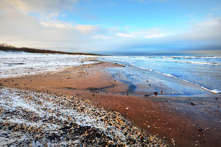 A view from the snow-covered Baltic sea shore with lots of seashells. Riga bay, Latvia. Colorful dramatic cloudscape. Fickle weather, waves, water splashes. Winter tourism, global warming