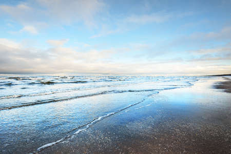 A view from the snow-covered sandy Baltic sea shore at sunset. Riga bay, Latvia. Dramatic sky. Crystal clear blue water. Fickle weather, waves and water splashes. Winter tourism, global warming theme Zdjęcie Seryjne