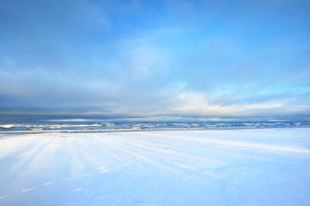 A view of the snow-covered Baltic sea coast at sunset. Coniferous forest in the background. Stunning cloudscape. Fairy blue evening light. Latvia
