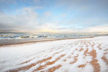 A view from the snow-covered Baltic sea shore at sunset. Riga bay, Latvia. Colorful dramatic cloudscape. Fickle weather, waves and water splashes. Winter tourism, global warming theme Zdjęcie Seryjne