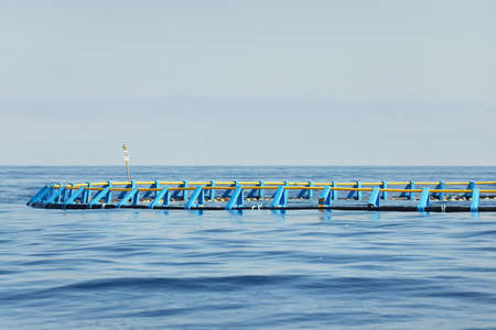 Fish farm in an open Mediterranean sea, close-up, Spain. Food industry, traditional craft and alternative production, environmental damage and conservation