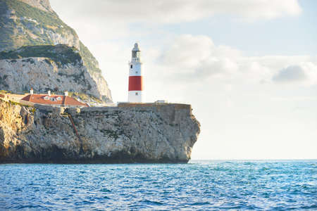 Trinity lighthouse at the rocky shore (cliffs) of the Europa Point. British Overseas Territory of Gibraltar, Mediterranean sea. National landmark, sightseeing, travel destination, famous place, travel