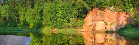 Panoramic view of sandstone cliffs and evergreen forest in Gauja national park, Latvia. Idyllic summer scene. Symmetry reflections in the water. Travel destinations, national landmarks, eco tourism