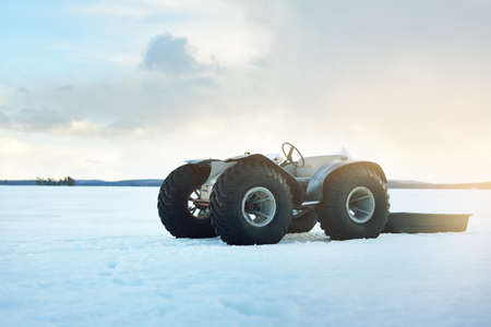 Hand made all terrain vehicle, close-up. Snow-covered frozen lake. Winter rural landscape. Dramatic sunset sky. Transportation, special equipment, dangerous driving, logistics, off-road Foto de archivo