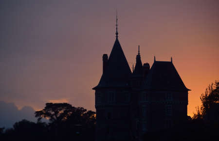 The tower and spire of Château de Pornic against epic sunset sky with bright pink and purple clouds. Dramatic cloudscape. Brittany, France. Travel destinations, sightseeing theme