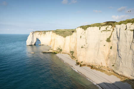 Picturesque panoramic aerial view of the Etretat white cliffs at sunset. Dramatic sky, azure water. Summer vacations in Normandy, France. Travel destinations, national landmark, sightseeing, history 免版税图像