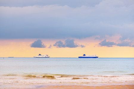 Large ships sailing near the coast of France at the Strait of Dover (Cap Blanc Nez, Pas de Calais) during sunset. Picturesque panoramic view. Epic cloudscape. Travel destinations, tourism, cruise Reklamní fotografie