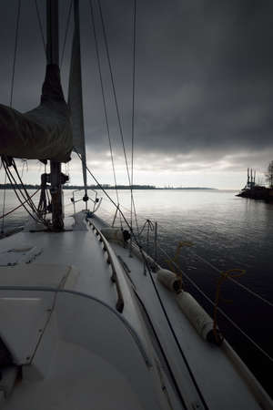 White yacht leaving the river port after the rain. A view from the deck to the bow and sails. Dark dramatic sky. Summer sailing. Leisure activity, sport, recreation, cruise concepts