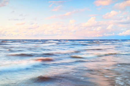 Epic colorful glowing pink sunset clouds above the sea after a thunderstorm. Dramatic sky. Waves and water splashes texture. Idyllic seascape. Concept image, long exposure. Picturesque scenery Stok Fotoğraf