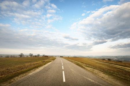 An empty asphalt road (highway) through the fields. Dramatic sky. France, Europe. Transportation, logistics, travel destinations, tourism, driving, speed, freedom, lockdown 스톡 콘텐츠