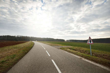 An empty asphalt road (highway) through the fields, street sign close-up. Dramatic sky. France, Europe. Transportation, logistics, travel destinations, tourism, driving, speed, freedom, lockdown