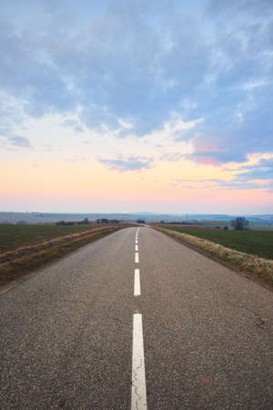 An empty asphalt road (highway) through the fields at sunset. Dramatic sky with colorful glowing clouds. France, Europe. Transportation, logistics, travel destinations, tourism, freedom, lockdown