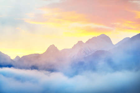 Mountain peaks in a morning fog at sunrise. Clear colorful sky with glowing clouds, pure sunlight. Epic cloudscape. French Alps, Ecrins massif, France