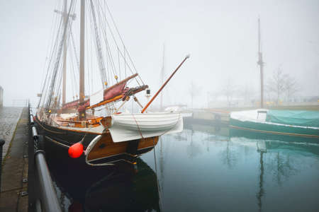 Vintage wooden yachts and fishing boats moored to a pier, close-up. Heavy morning fog. Germaniahafen, Kiel, Germany