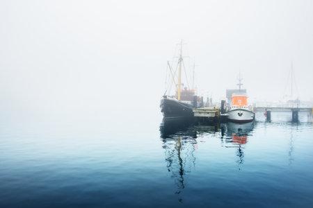 Fishing boats moored to a pier, close-up. Heavy morning fog. Kiel, Germany 스톡 콘텐츠