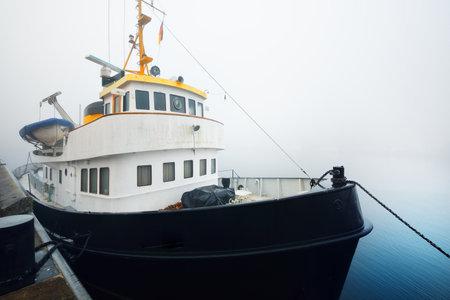 Tug boat moored to a pier, close-up. Heavy morning fog. Kiel, Germany