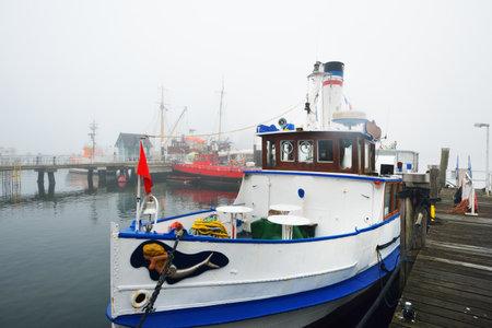 Passanger steamer moored to a pier, close-up. Heavy morning fog. Kiel, Germany