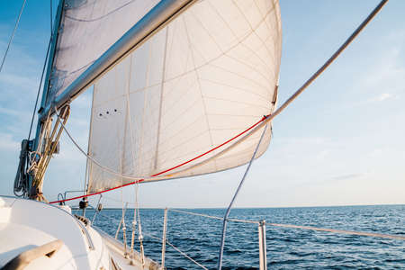Sloop rigged yacht sailing in an open Baltic sea on a clear day. Close-up view from the deck to the bow, mast and sails. Latvia
