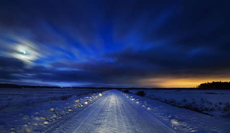 Winter landscape. Snow-covered country road through the fields at night. Forest in the background. Terrific sunset sky with colorful clouds. Latvia Stok Fotoğraf
