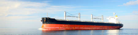 Large cargo ship sailing in a still sea water on a clear day. Panoramic view. Freight transportation, global communications, logistics, industry, business, economy, environmental damage