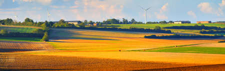 Golden plowed reaped agricultural field, wind turbines in the background. France, Europe. Panoramic aerial view. Environmental conservation, farm and food industry, ecology, alternative energy