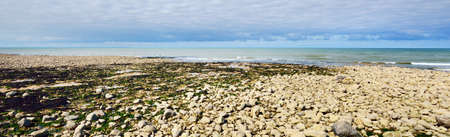 D-Day landing coastline in Normandy, France. Pebble texture close-up. Dramatic sunset sky. Travel destinations, landmarks, tourism, vacations, cruise, nature, environment. Panoramic view