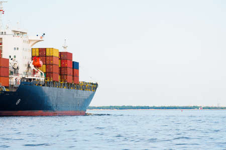 Large cargo container ship leaving the port of Norfolk, close-up. Cloudy blue sky. Virginia, USA