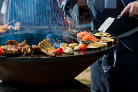 Man is cooking a grilled meat, fish and vegetables, close-up. Charcoal grill. Latvia