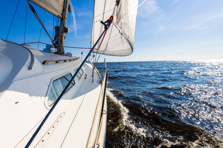 White yacht sailing in an open Baltic sea on a clear sunny day. A view from the deck to the bow, mast and sails. Waves and water splashes. Estonia