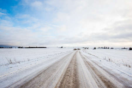A road through the snow-covered country fields at sunset. Sunny winter day