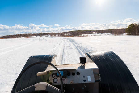 A hand made all terrain vehicle on the snow-covered field, close-up. Winter country landscape. Karelia North, Lapland, Kuito lake
