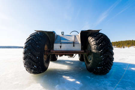 A hand made all terrain vehicle standing on the frozen river, close-up. Winter country landscape. Karelia North, Lapland