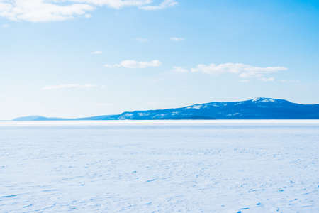 Panoramic view of the frozen lake. Snow-covered mountains and coniferous forest in the background. Clear blue sky. Kola Peninsula, Murmansk region, Polar Circle, Karelia, Russia