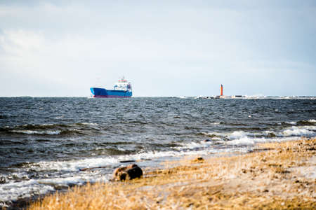 Large blue cargo ship in the Baltic sea. Waves and stormy clouds. Baltic sea, Latvia