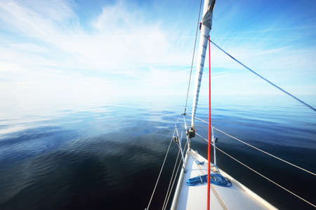 White sloop rigged yacht sailing in an open Baltic sea on a clear sunny day. A view from the deck to the bow. Estonia